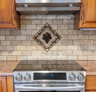 grape and wandering vine mosaic tile medallion centerpiece above stove